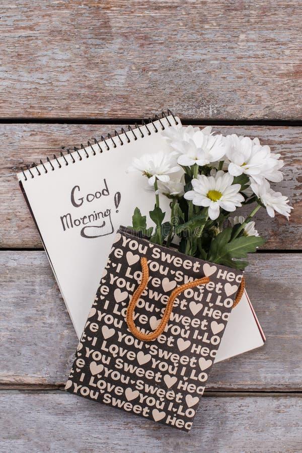 Notizblock mit Wunsch und Blumen des guten Morgens lizenzfreie stockfotos