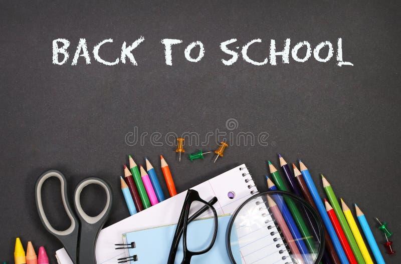 Notizbuch, Übungsbuch, Scheren und Bleistifte auf schwarzem Brett lizenzfreies stockbild