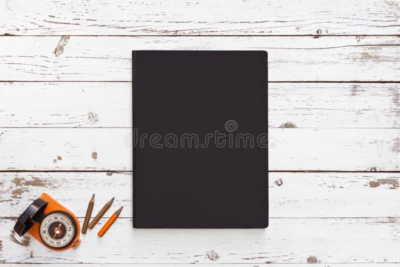 Notizbuch auf dem weißen Holztisch mit Kompass und Bleistiften lizenzfreie stockbilder