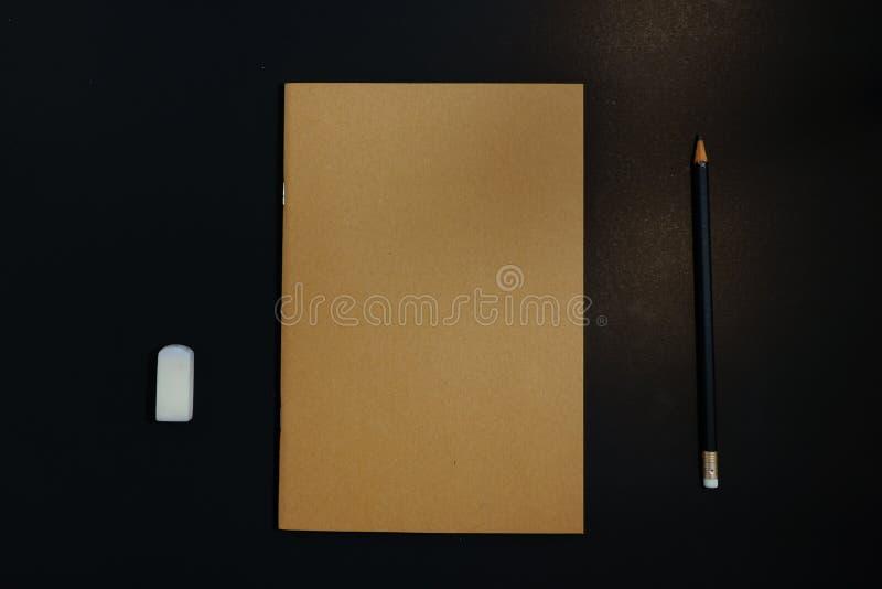 Notizbuch, Bleistift und Radiergummi auf schwarzem Hintergrund lizenzfreie stockfotos
