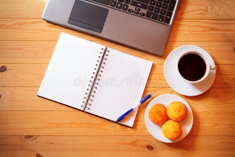 Notizbuch, Laptop, frische Kuchen und ein weißer Tasse Kaffee stockbilder