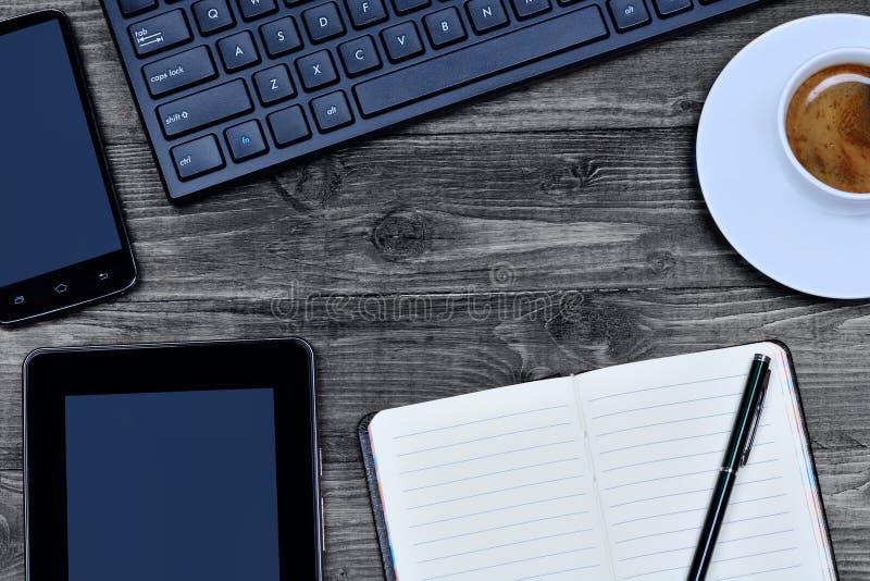 Notizbuch mit digitaler Tablette, Telefon und Kaffee auf Tabelle lizenzfreie stockbilder