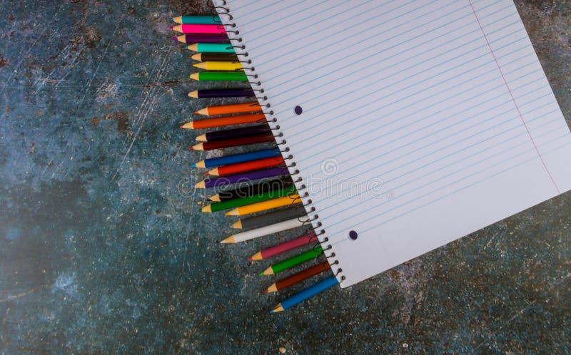Notizbuch mit Farbbleistift auf blauer Tabelle, Draufsicht stockfoto