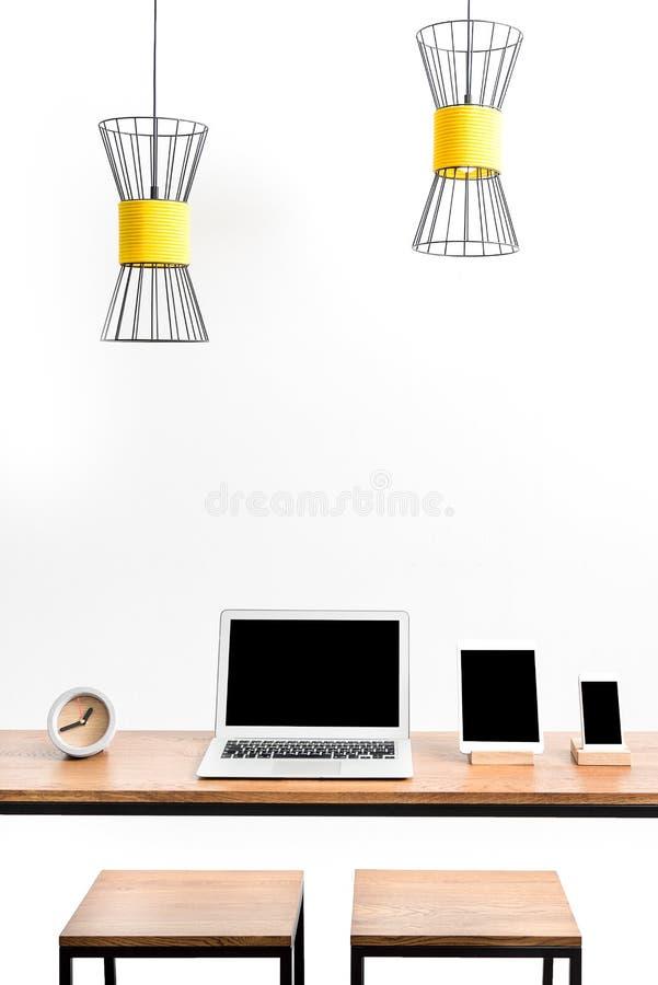 Notizbuch mit Gerät und Smartphone auf Tabelle mit Stühlen lizenzfreies stockfoto