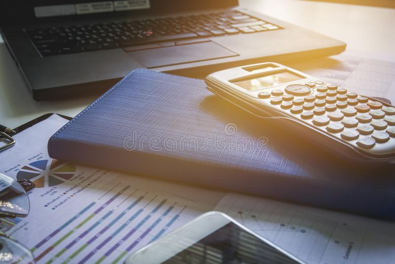 Notizbuch mit Geschäftsdiagrammen und Diagramme berichten, Taschenrechner auf Schreibtisch der Finanzplanierung stockfoto