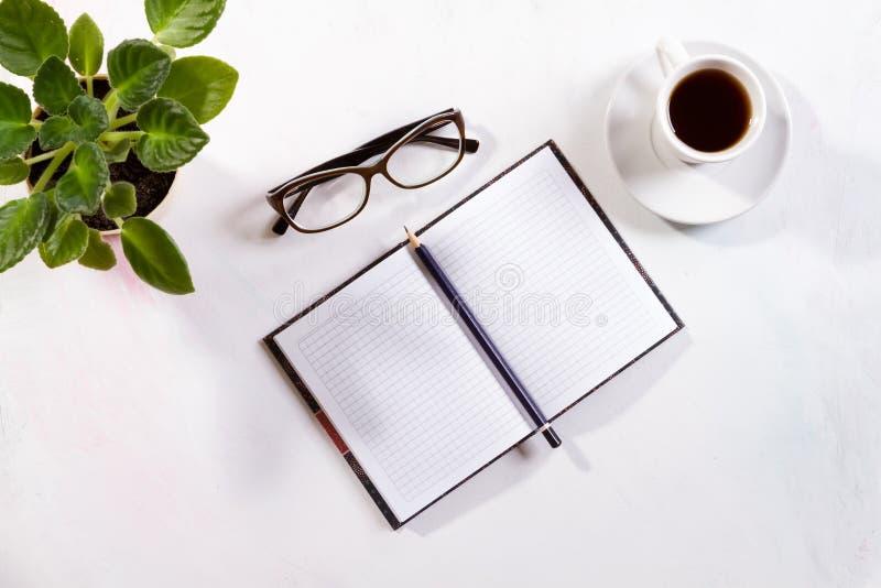Notizbuch mit Gläsern und Kaffee auf Tabelle lizenzfreies stockbild