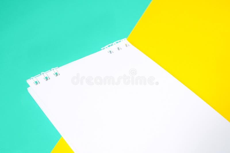 Notizbuch mit Weißbuch auf mehrfarbigem Hintergrund mit Gelbem und Blauem stockbild