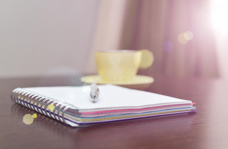 Notizbuch, Stahlstift und färben sich auf dem Tisch mit Sonnenlicht gelb lizenzfreie stockfotos