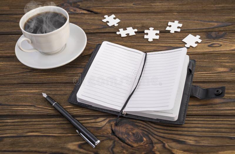 Notizbuch, Stift, Puzzlespiel und heißer Kaffee auf einem Holztisch lizenzfreies stockbild