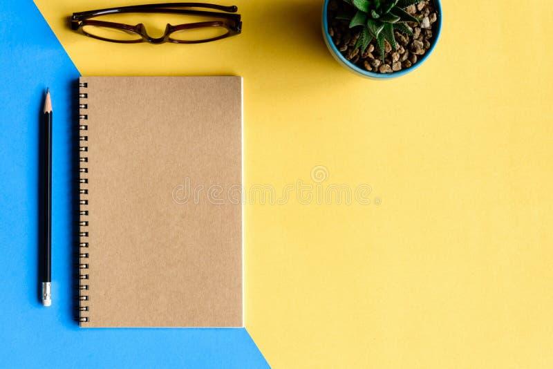 Notizbuch und Bleistift auf gelbem Schreibtisch stockbilder