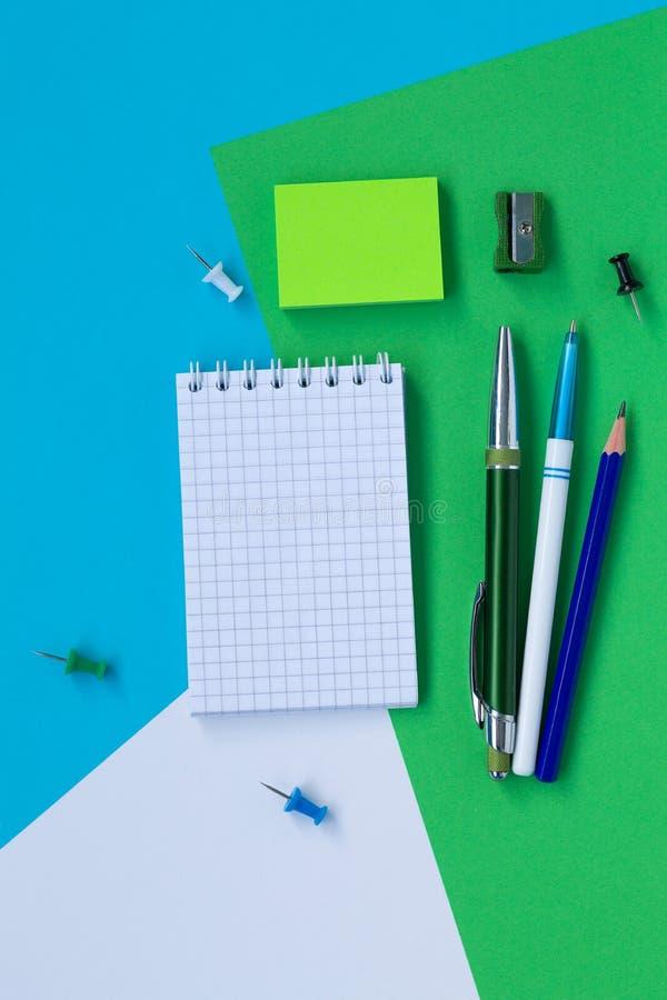 Notizbuch und Bleistift lokalisiert auf Draufsicht des weißen, blauen und grünen Hintergrundes lizenzfreie stockbilder
