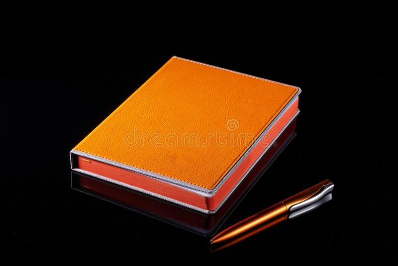Notizbuch und Stiftleuchtorange auf einem schwarzen Hintergrund stockfotografie