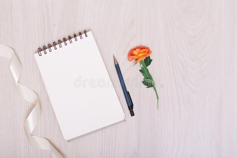 Notizbuchpapier, Stift und purpurrote trockene Blumen auf weißem Hintergrund stockfoto
