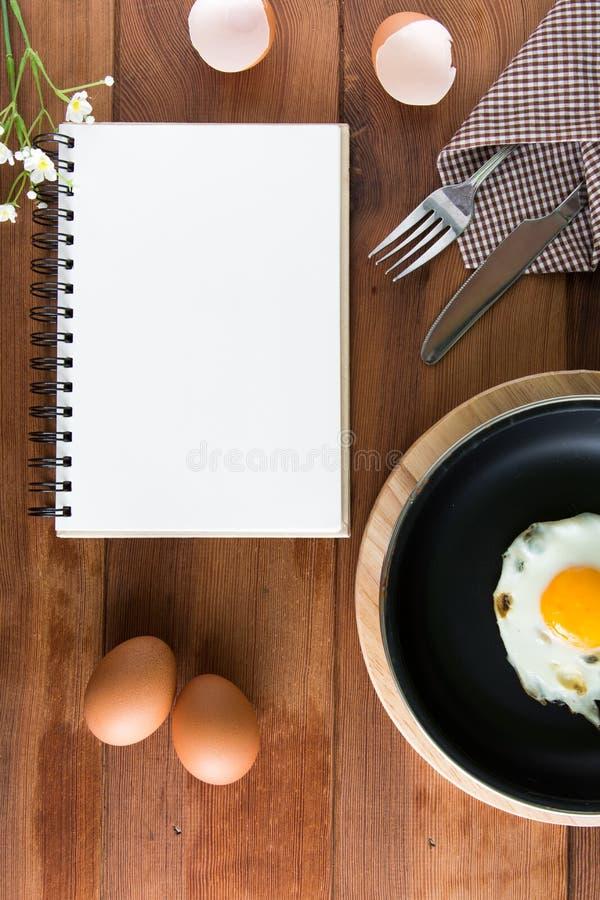 Notizbuchweiß auf einem Bretterboden mit Ei lizenzfreies stockfoto