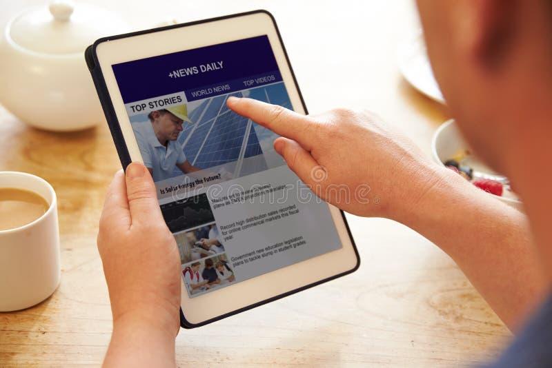 Notizie App di Person At Breakfast Looking At sulla compressa di Digital immagini stock