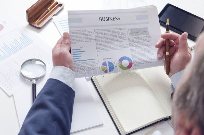 Notizie dal mondo degli affari d'esame dell'uomo d'affari maturo nel suo luogo di lavoro immagine stock libera da diritti