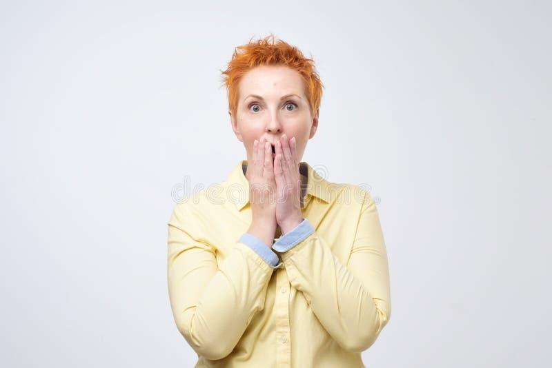 Notizie scioccanti Donna matura sorpresa con la bocca rossa della copertura dei capelli con la mano e fissare alla macchina fotog fotografia stock libera da diritti