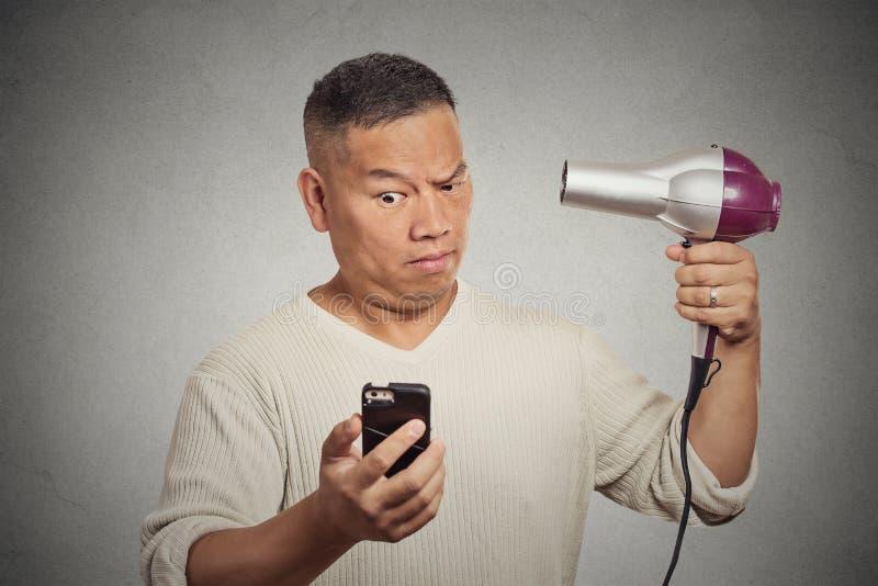Notizie sociali sorprese di media della lettura dell'uomo sul hairdryer della tenuta del telefono fotografia stock