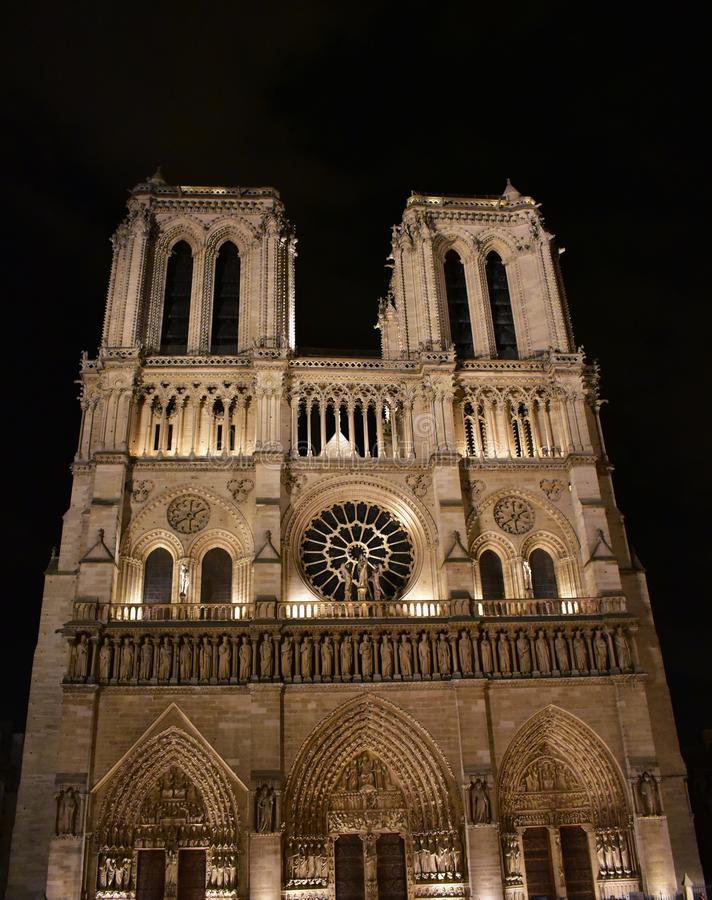 Notre Dame Cathedral a la medianoche Fachada, torres, ventana color de rosa, archs y estatuas París, Francia foto de archivo