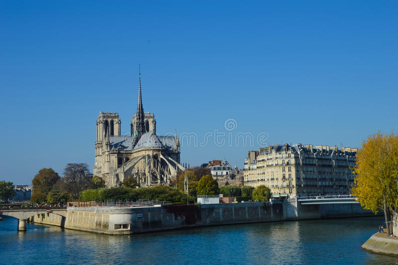 Notre Dame cathedral next to the river of Paris with boats and buildings summertime stock image