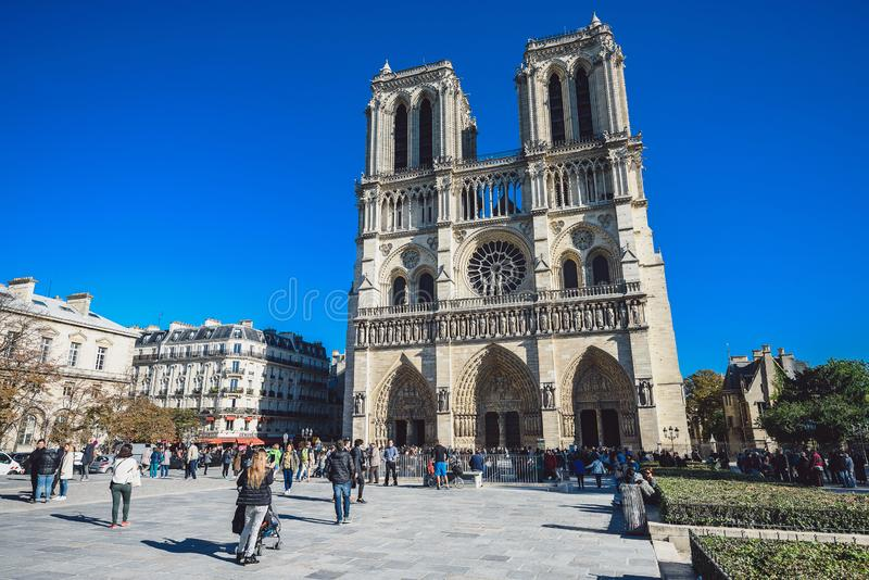Notre Dame Cathedral and tourists visiting on sunny day stock images