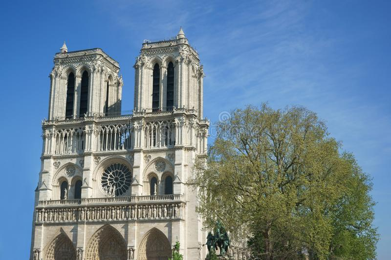 Notre-Dame de Paris West towers Blue sky Tree. Cathedral Basilica Notre Dame of Paris, west towers on a blue sky background. The Charlemagne statue near the tree royalty free stock images