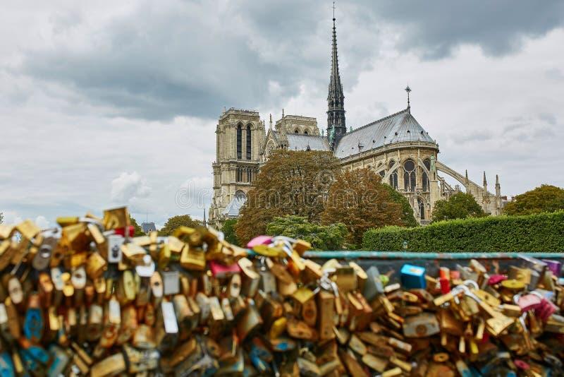 Notre-Dame y muchas aman las cerraduras en el puente en París fotografía de archivo