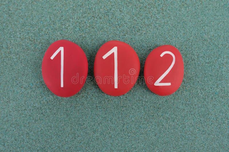 112, Notruftelefonzahl verfasst mit roten farbigen Steinen über grünem Sand lizenzfreies stockbild