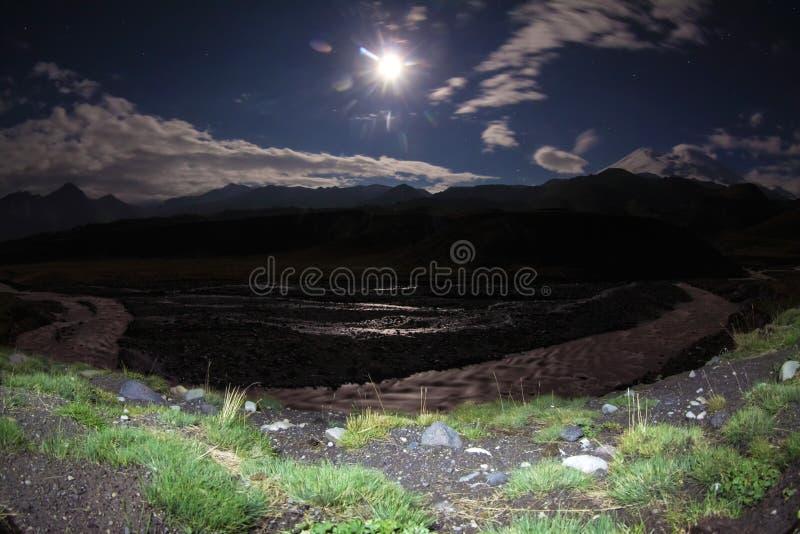 Notte della luna piena con i fasci sopra la grande radura della montagna con il fiume immagine stock