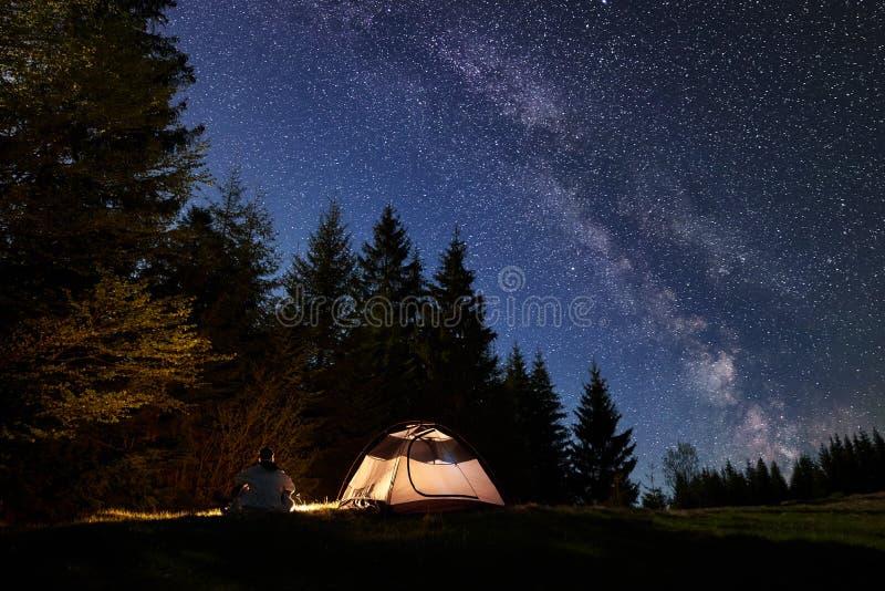 Notte maschio del enjoyng della viandante che si accampa vicino alla tenda turistica al fuoco di accampamento in corso il cielo e immagini stock libere da diritti