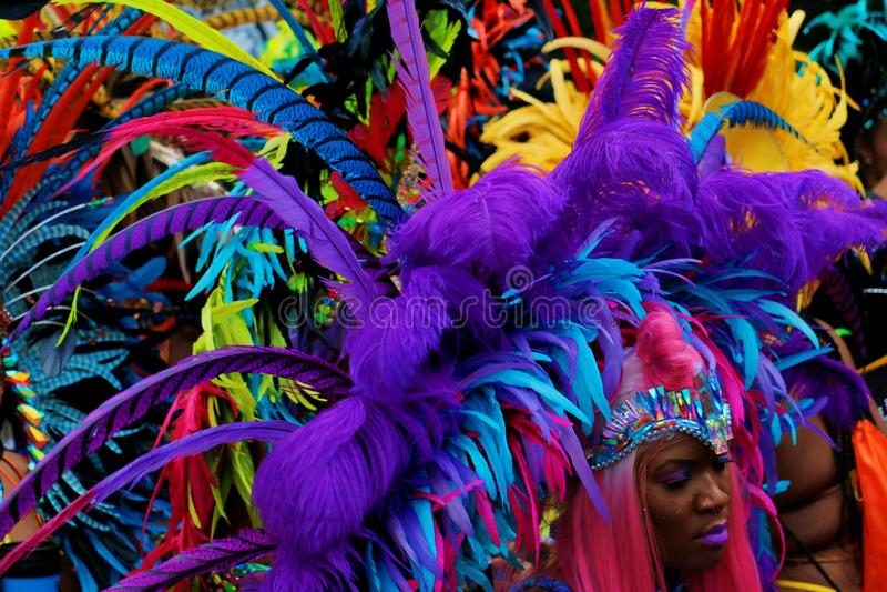 NOTTING HILL, LONDRES - 27 DE AGOSTO DE 2018: Carnaval de Notting Hill, porciones de plumas grandes en el casco de la mujer en de foto de archivo libre de regalías
