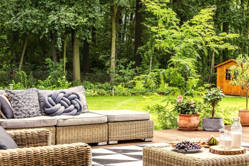 Nouez l'oreiller sur un sofa, la table avec du lait et le fruit dans un esprit de jardin photographie stock libre de droits