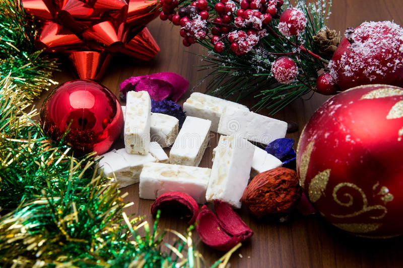 Nougat, traditional Spanish sweet for Christmas. sweet almond nougat dark background with snow and fir decorations. Nougat, traditional Spanish sweet for royalty free stock photo