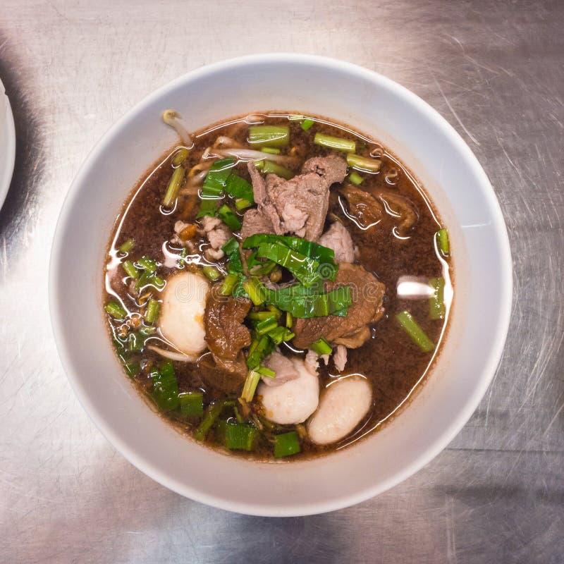 Nouille de porc et dessus noir de soupe avec la boulette de viande et les légumes dans la cuvette blanche photographie stock libre de droits