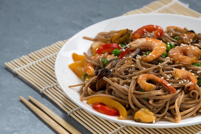 nouilles épicées de sarrasin avec des fruits de mer et des légumes dans le plat photo libre de droits