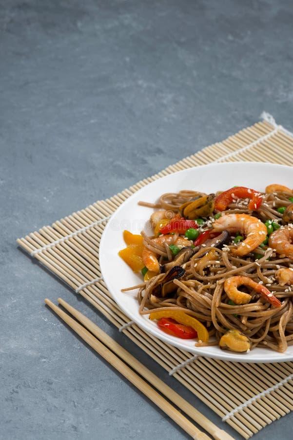 Nouilles épicées de sarrasin avec des fruits de mer et des légumes dans le plat, VE image libre de droits
