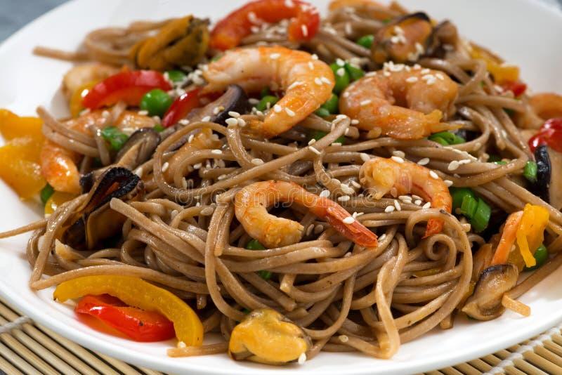 nouilles épicées de sarrasin avec des fruits de mer et des légumes, plan rapproché images libres de droits