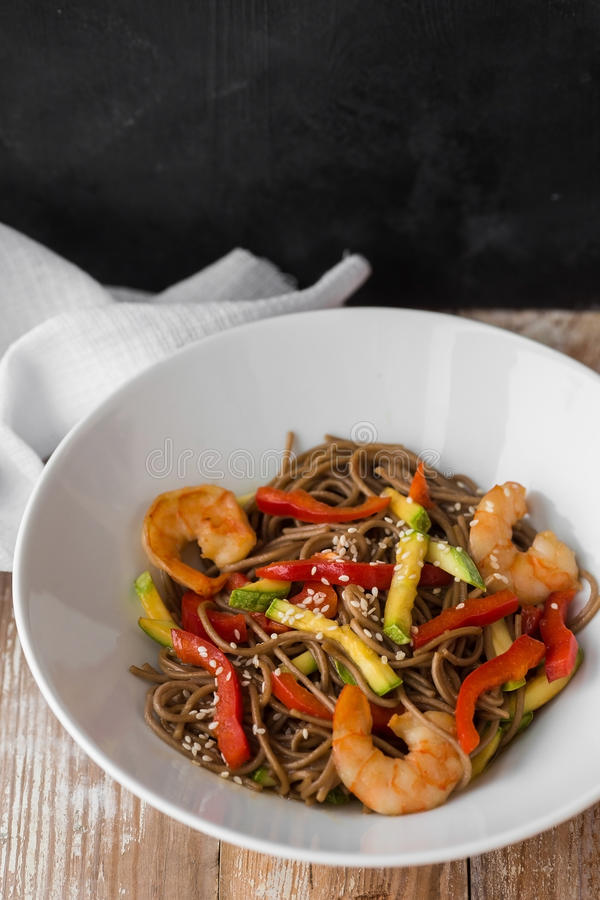 Nouilles avec des légumes et des fruits de mer sur les nouilles en bois d'un style chinois de table avec des légumes et des fruit images libres de droits