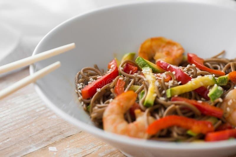 Nouilles avec des légumes et des fruits de mer sur les nouilles en bois d'un style chinois de table avec des légumes et des fruit images stock