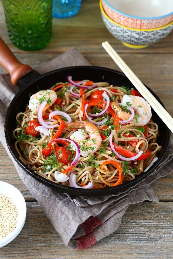 Nouilles chinoises de sarrasin avec la crevette épicée dans une poêle images stock