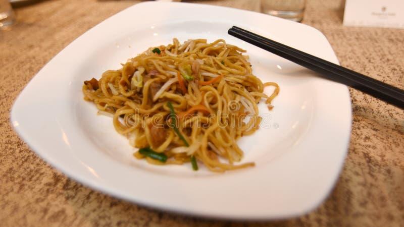 Nouilles dans un plat sur la table à servir image stock