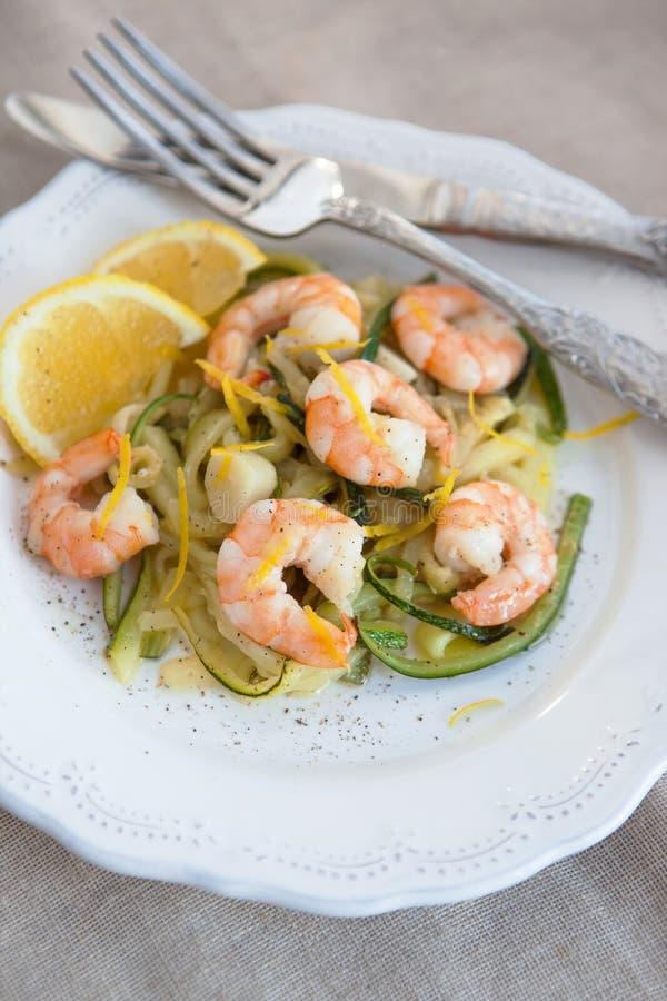 Nouilles de courgette avec des crevettes roses et le zeste de citron images stock