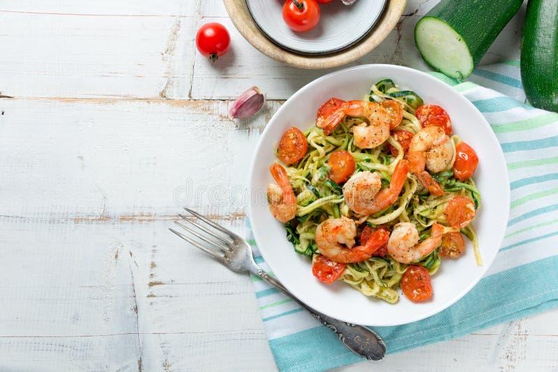 Nouilles de courgette faites sauter avec la tomate-cerise et les crevettes roses photos libres de droits