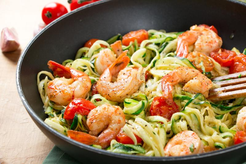 Nouilles de courgette faites sauter avec la tomate-cerise et les crevettes roses dans une casserole photo stock