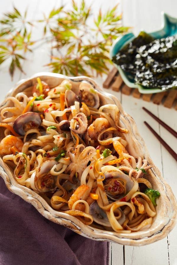 Nouilles frites avec les mollusques et crustacés, le calmar et le calamari images libres de droits