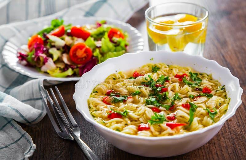 Nouilles instantanées dans un bol blanc sur fond de table en bois et salade de légumes image stock