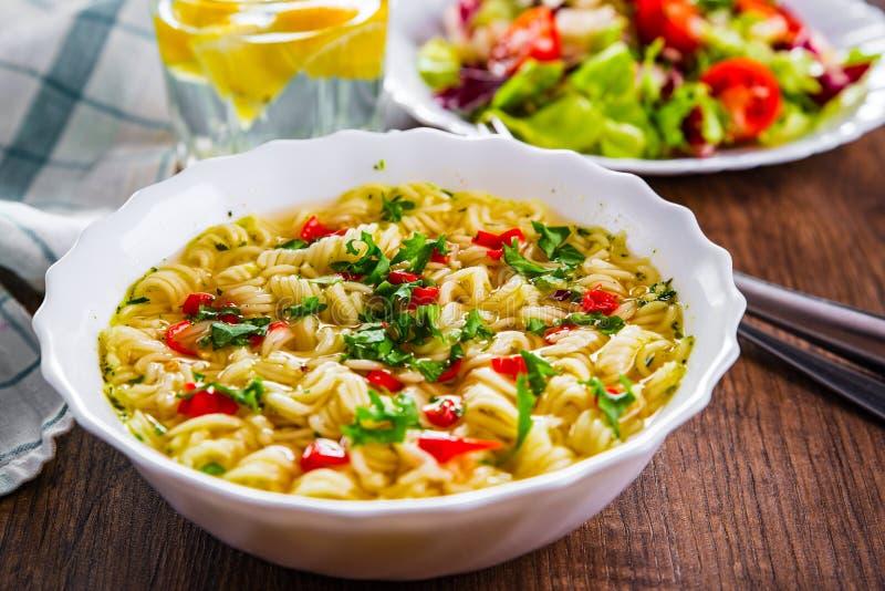 Nouilles instantanées dans un bol blanc sur fond de table en bois et salade de légumes photo libre de droits