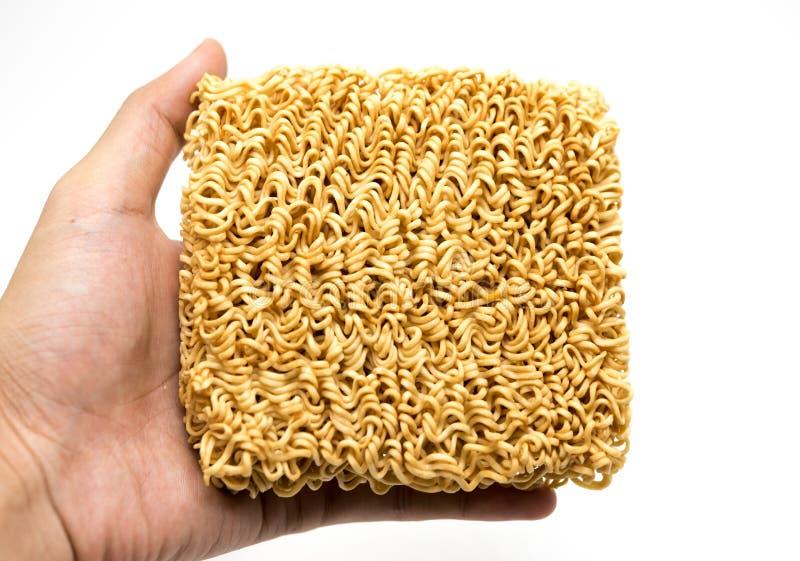 Nouilles instantanées de ramen asiatiques dans des mains sur le backgroun blanc image libre de droits