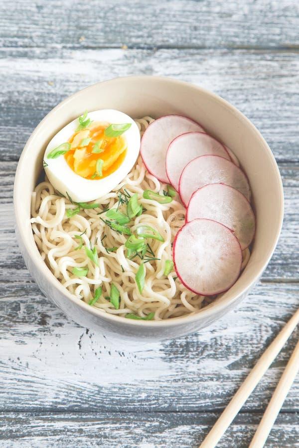 Nouilles instantanées sur le fond en bois Nouilles instantanées chinoises cuites Ramen de soupe avec l'oeuf et le radis image stock