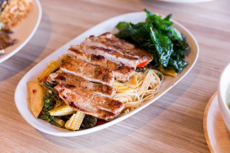 Nouilles ivres : La nouille d'oeuf au plat épicée avec le basilic et le poivre a servi avec du porc grillé images stock